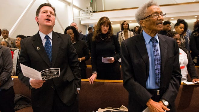 Phoenix Mayor Greg Stanton (left) and former Phoenix Councilman Calvin Goode sing during a Martin Luther King Candlelight Ceremony Concert at Pilgrim Rest Baptist Church in Phoenix on Jan. 17, 2016.