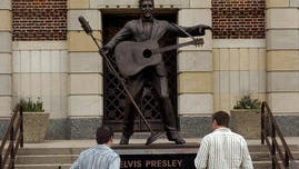 Two visitors to Municipal Auditorium look over the statue of Elvis Presley in front of the building.