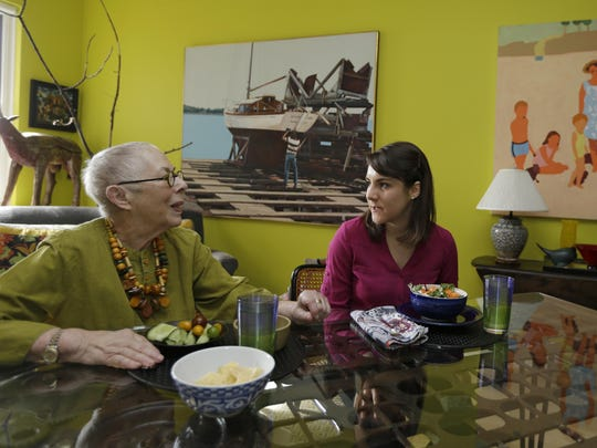 In this Friday, Feb. 17, 2017 photo, Laura Berick, left, a retired art dealer, has lunch with Justine Myers at Berick's home in Judson Manor, in Cleveland. The arrangement is aimed at reducing the social isolation often experienced by the elderly and bridge the gap between young and old. Myers is an artist-in-residence at Judson Manor.