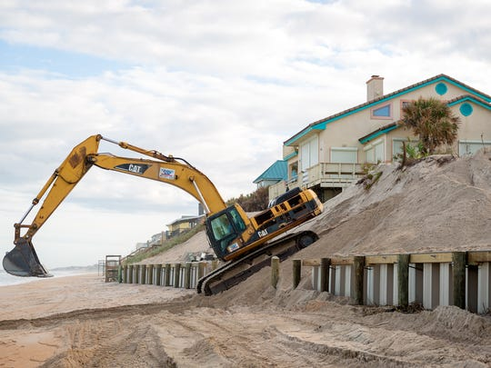 An excavator is used to build a sea wall in Vilano Beach, Fla. in December 2015.