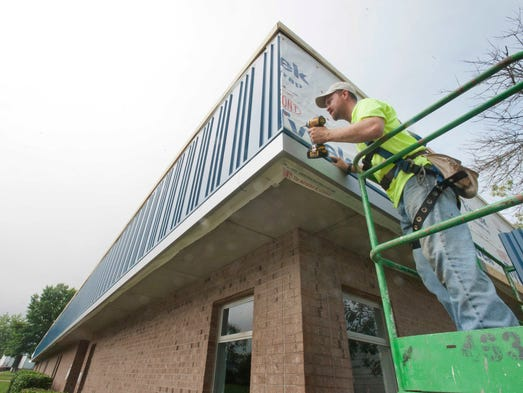 Sheet metal worker Dustin Smith with Kalkreoth Roofing and Sheet Metal installs sidewall panels onto the new Oldham County Middle School addition. 18 August 2014
