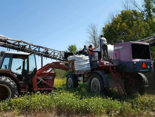 Seeds for a cover crop are loaded into farming equipment.