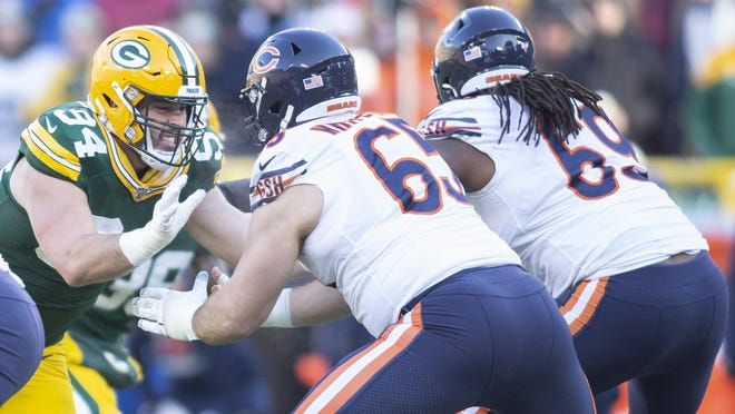 Green Bay Packers defensive lineman Dean Lowry, left, fights off a double team by the Chicago Bears on Dec. 15, 2019.
