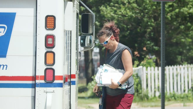 USPS mail carrier Torri Followell checks items as she walks around her truck on her route Wedensday.
