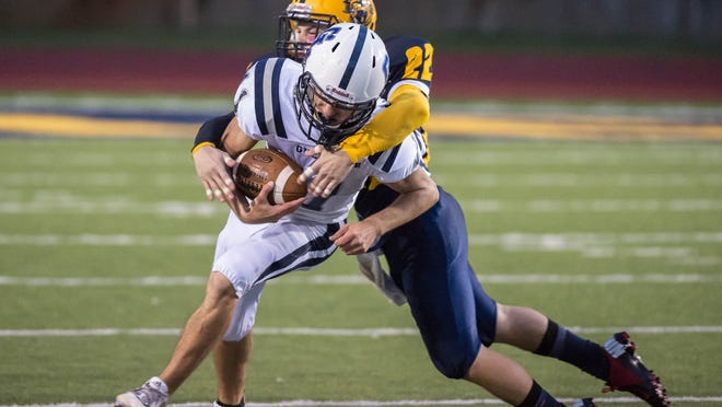 Battle Creek Central junior Michael Gray tackles Gull Lake quarterback Seth Eldridge in action on Friday as the Bearcats came up with a win.