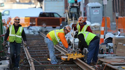 In this photo from December, workers lay tracks on Elm Street for the streetcar line.