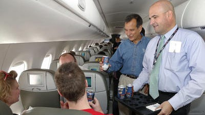 In this July 2013 file photo Jim Koch, founder and brewer of Samuel Adams, left, and Marty St. George, senior vice president of marketing and commercial at JetBlue, hand out Boston Lager cans on the inaugural JetBlue flight from Boston to New York. As the airline industry works to improve its food and beverage options, a new trend has emerged -- airlines adding craft beers to their in-flight offerings.