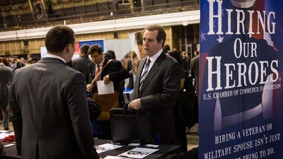 A veteran speaks to a job recruiter at a 'Hiring our Heroes' Job Fair on March 27, 2014 in New York City. The Labor Department says employers added 192,000 jobs, slightly below February's total of 197,000. Employers also added a combined 37,000 more jobs in February and January than previously estimated.