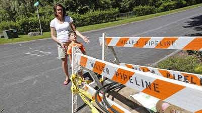 Mary Lynn Strom and her son Matthew, 5, stand next to a unconnected gas line next to her home in Cortlandt Manor on June 16, 2014. Con Edison and the Town of Cortlandt are disputing how best to install the line which is close to a water main that Con Edison thinks it might hit if they don't excavate a small section of the street to guarantee a safe install. The town wants to charge Con Edison $40,000 for the small exploratory excavation because they claim Con Ed had a opportunity to install the line before the street was paved.