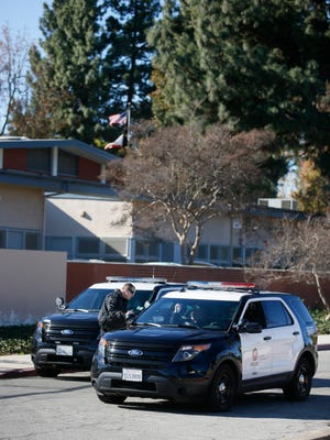 Police officers talk as they patrol around William Mulholland Middle School as the school remains closed Tuesday.