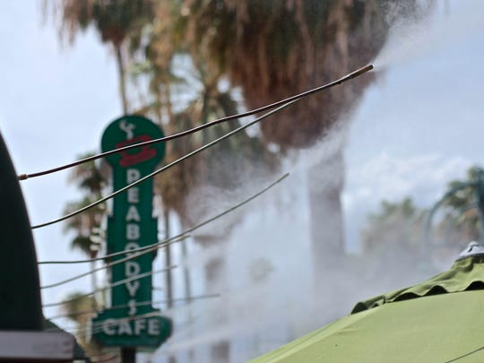 Water misters operate near Peabody's Cafe in downtown Palm Springs on July 31, 2015.