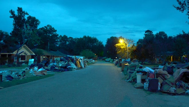 Night falls on debris-lined streets in Denham Springs on Friday, Aug. 19, 2016.  Residents alongside volunteers will continue the clean up and restoration efforts for weeks and months to come.