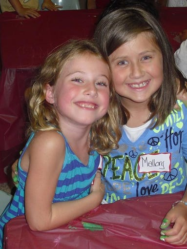 Summer camp is a great place to make new friends. Mayson Morgan, 6, (l) and Mallory Yirsa, 7, take a break from activities to pose for the camera. Both girls go to school in Grand Ledge.