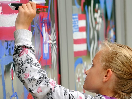 Children and adults paint the windows of the Manitowoc