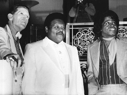 FILE - This Jan. 23, 1986 file photo,  from left, musicians Jerry Lee Lewis,  Fats Domino and James Brown pose at a reception where they were inducted into the Rock and Roll Hall of Fame at the Waldorf-Astoria Hotel in New York.  Domino, the amiable rock 'n' roll pioneer whose steady, pounding piano and easy baritone helped change popular music even as it honored the grand, good-humored tradition of the Crescent City, has died. He was 89. Mark Bone, chief investigator with the Jefferson Parish, Louisiana, coroner's office, said Domino died Tuesday, Oct. 24, 2017. (AP Photo/G. Paul Burnett)