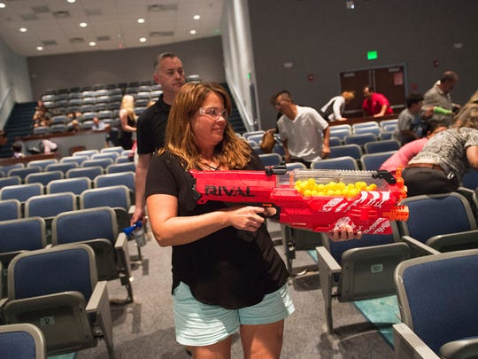 "Volunteer Christina Papada (front), of Palm City, plays the role of an active shooter as Chad Cunningham (back), a national trainer for the ALICE Training Institute, walks behind monitoring the reactions of volunteer victims during an interactive role playing scenario involving an active shooter, during The ALICE Training Institute's training for parents on surviving a school shooting, at Martin County High School's auditorium on Monday, April 30, 2018, in Stuart. Papada has two children at Palm City Elementary School. ""It's nerve wracking and now is the time to learn and teach our kids what to do,"" said Papada about attending the class."