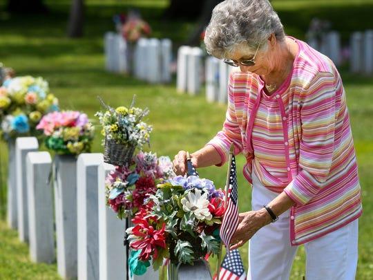 Evansville resident Sophie Husak decorates the grave of her husband for 54 years, Marine Korean War veteran John Husak, at Evansville's Oak Hill Cemetery Sunday, May 27, 2018.