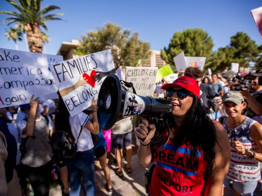 "A member of the Patriot Movement Arizona yells ""Trump is your president"" through a megaphone on June 30, 2018, during the Families Belong Together rally outside of the Arizona State Capitol in Phoenix, Arizona."