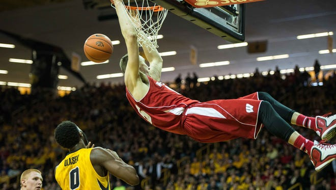 Wisconsins forward Sam Dekker (15) hangs on the rim above Iowa Hawkeyes center Gabriel Olaseni (0).
