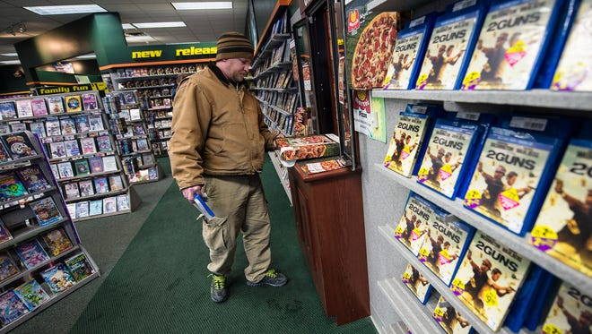 """Mike Patenaude, of Green Bay, Wis., picks up his pizza at the Marco's Pizza """"drive-thru"""" window that opens up to a Family Video store in Green Bay, Wis. Family Video has started leasing space to other retailers as a way to combat the digital streaming wave."""