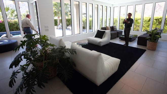 Real estate agent Kip O'Connor (right) takes a photo during a broker's open house at 1375 North Rose Ave. in the Vista Las Palmas area of Palm Springs, Calif., on March 23, 2016, as another agent, Bill Cochran (left), walks through the home to an outdoor patio. The home, which is listed by agent Scott Histed of Bennion Deville Homes, was recently lowered from $1,815,000 to $1,650,000.