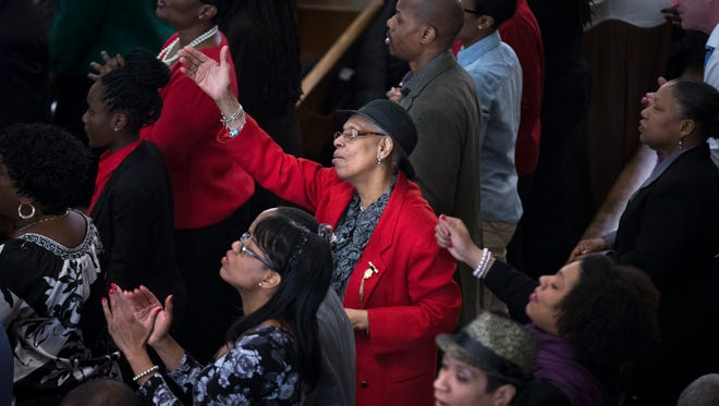 """A parishioner attends Sunday services at the Bethel Gospel Assembly as the congregation mourns the deaths of two members in Wednesday's explosions in the East Harlem neighborhood of New York. New York City Mayor Bill de Blasio said the women lost """"were examples to all of us"""" because of the faith and spirit they demonstrated."""