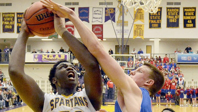 Caleb Swanigan of Homestead is fouled on the shot by Erik Bowen of Kokomo, 3rd quarter of the 4A regional in Marion, Saturday.    Samuel Hoffman/ The Ft Wayne Journal Gazette