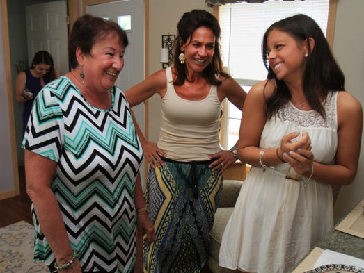 ASB 0603 BCC Designers  Olivia DeCellio, left, reacts after entering her newly decorated home from Brookdale design team students, Natalie Rosenthal, center, and Brittany Bevilacqua, 20, right, of Freehold. Brookdale students are judged for the interior design of homes provided for by the Affordable Housing Alliance to Sandy displaced home owners, at Pine Tree Mobile Village in Eatontown, Wednesday, June 3, 2014. NJ - Photo by Mary Frank