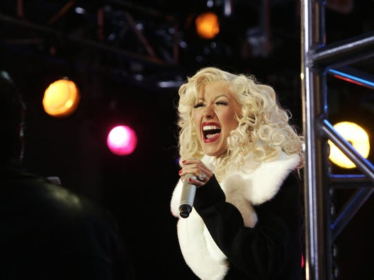 New York, UNITED STATES:  US pop star Christina Aguilera performs for the crowd in Times Square for New Year's Eve minutes before the famous ball drops from the flagpole atop One Times Square in New York, 31 December 2006, to ring in the year 2007 . Hundreds of thousands of revellers packed into New York's Times Square to ring in 2007, braving heightened security to join in the traditional centrepiece of New Year celebrations in the United States.    AFP PHOTO / Timothy A. CLARY  (Photo credit should read TIMOTHY A. CLARY/AFP/Getty Images)