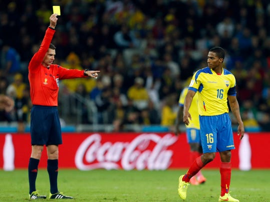 Referee Benjamin Williams, left, from Australia gives Ecuador's Antonio Valencia a yellow card during the group E World Cup soccer match between Honduras and Ecuador at the Arena da Baixada in Curitiba, Brazil, Friday, June 20, 2014. (AP Photo/Jon Super)