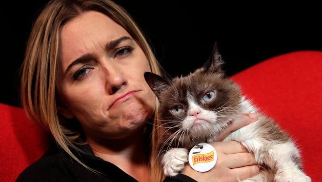 In this Nov. 14, 2016 photo, Grumpy Cat poses for photos with her owner Tabatha Bundesen in New York. The social media star posted her Top 10 pet peeves on her new blog at Pawculture.com.