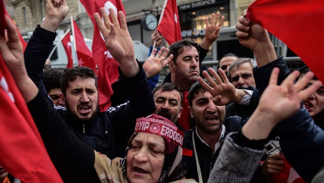 Protesters wave flags and give a four-fingered salute that shows solidarity with the Muslim Brotherhood during a protest in front of the Dutch consulate on March 12, 2017 in Istanbul.