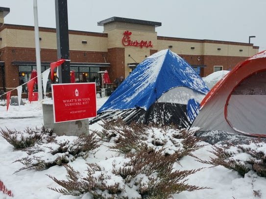 People camp out in the snow prior to the opening of