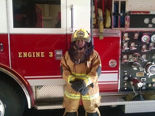 Yuma Firefighter stands in bee call uniform