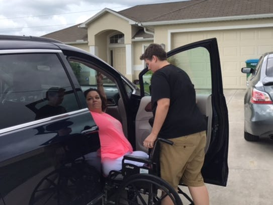 Danielle Hagmann is helped into a van by and her spouse,