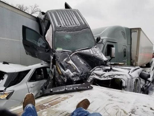 A truck rests on top of a semi-truck at an accident