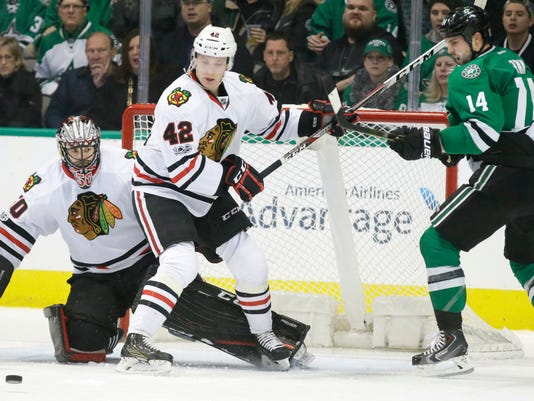 Chicago Blackhawks goalie Corey Crawford (50) and Gustav Forsling (42) defend the goal against Dallas Stars left wing Jamie Benn (14) during the first period of an NHL hockey game in Dallas, Saturday, Feb. 4, 2017. (AP Photo/LM Otero)