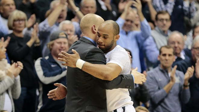 Xavier Musketeers guard Myles Davis (15) hugs head coach Chris Mack as he leaves the court following his triple double.