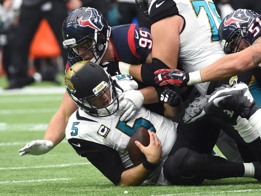 FILE - In this Jan. 3, 2016, file photo, Jacksonville Jaguars quarterback Blake Bortles (5) is sacked by Houston Texans defensive end J.J. Watt (99) during the second half of an NFL football game in Houston. The status of J.J. Watt is uncertain after he missed the entire preseason following surgery to repair a herniated disc in his back in July. (AP Photo/Eric Christian Smith, File)