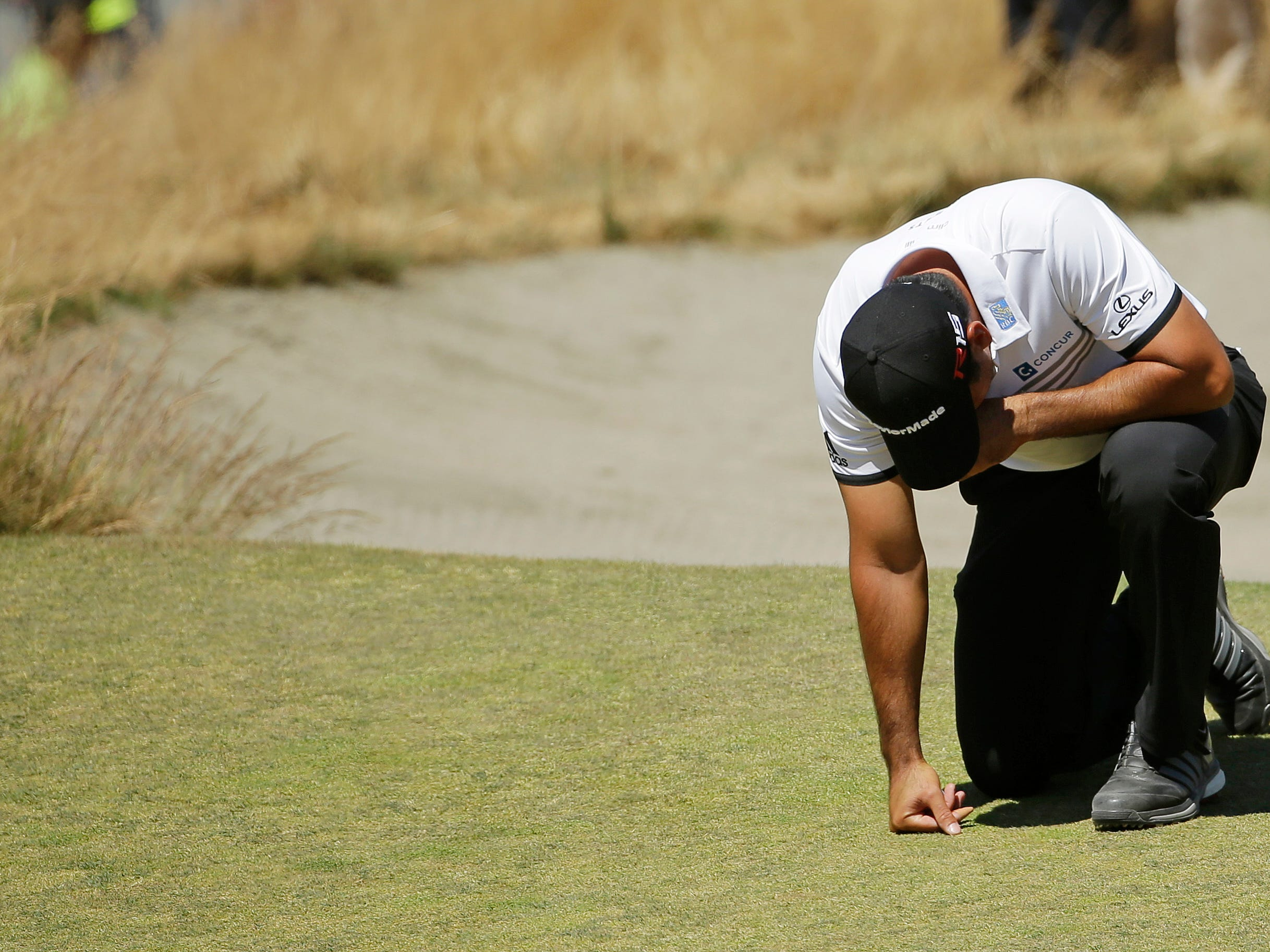 Jason Day, of Australia, kneels while waiting to putt on the ninth hole after having collapsed earlier in the fairway during the second round of the U.S. Open golf tournament at Chambers Bay on Friday, June 19, 2015 in University Place, Wash. (AP Photo/Ted S. Warren)