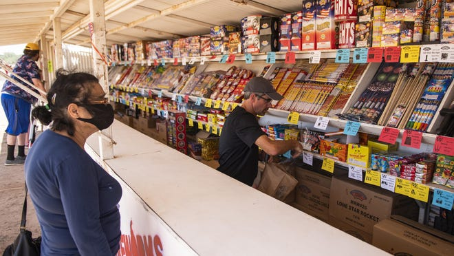 Jon Murray helps Alvina Reyna at the Mr. W fireworks stand on US Highway 62 in Lubbock County on Monday, June 29, 2020.