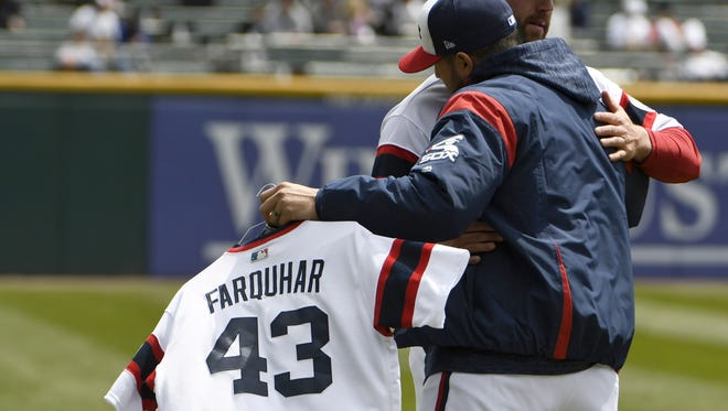 Hector Santiago, left, hugs Chris Volstad as he carries the jersey of Danny Farquhar to the bullpen before Sunday's game against the Astros.