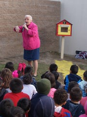 Lois Whitney tells students a story, with the Little