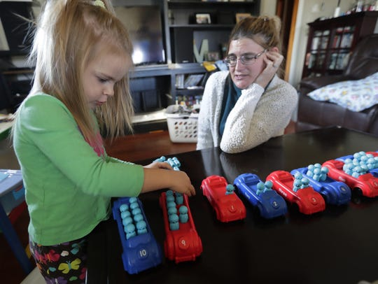 Addie Knedle, 2, works on her counting skills during