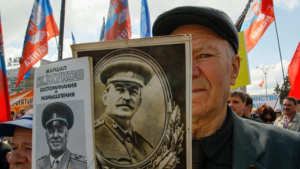A man holds portraits of former Soviet dictator Josef