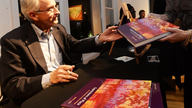 John Kemp signs his book Expressions of Place at the Artspace opening reception.