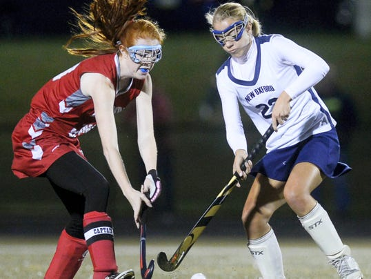 Bermudian Springs' Lindsey Brehm, left, and New Oxford's Carly Flickinger fight for the ball during Wednesday's YAIAA field hockey tournament semifinal at York Suburban High School.