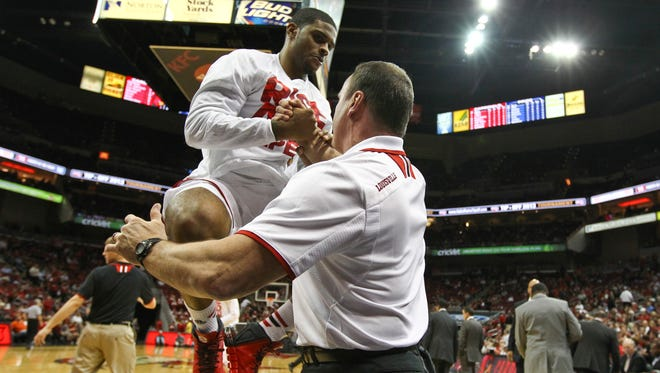 In this file photo from Nov. 2013, Chane Behanan gets an airlift up after stretching by strength coach Ray Ganong before the start of the second half Tuesday night. Louisville rolled past Hofstra 97-69 at the KFC Yum! Center.