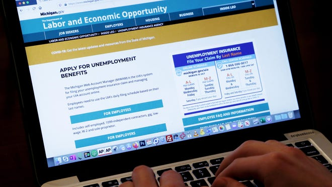 An unemployed worker checks looks at the State of Michigan unemployment site, Wednesday, April 29, 2020, in Detroit. Gov. Gretchen Whitmer on Monday offered little hope regarding state help for restaurant and other workers who may lose their jobs as a result of new coronavirus restrictions announced Sunday, saying Michigan's finances are also tight.
