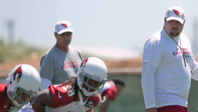 Cardinals outside linebacker coach James Bettcher looks over Andre Ellington as he lines up during OTAs in Tempe on June 3, 2013.